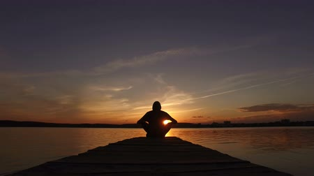 The guy goes to the pier on the lake at sunset and sits down in the lotus position.