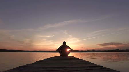 Silhouette of a man at sunset comes to the pier on the lake and sits down in a lotus pose.