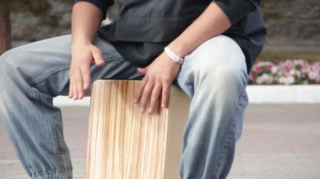A street drummer musician plays a percussion instrument Cajon.