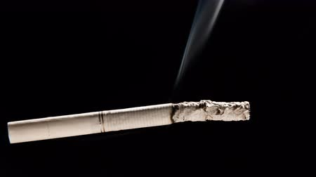 A white cigarette with a white filter burns, smoldering and smoke on a dark background Close-up. Time lapse.