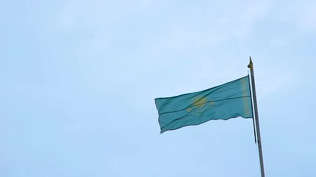 Flag of the Republic of Kazakhstan on the flagpole waving on background blue sky. Wideo