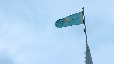 Flag - the symbol of the Republic of Kazakhstan on the flagpole develops on the background of blue sky with clouds. Wideo