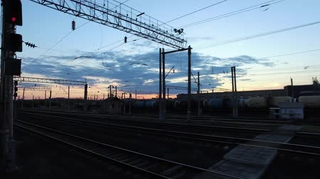 The train is approaching the railway station in the background of a sunset by the side of a freight train standing on the neighboring tracks.