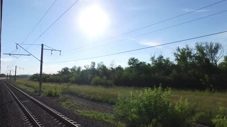 A view from the first train car towards the sun, which shines after a turning passenger train along the railway among green trees. Wideo