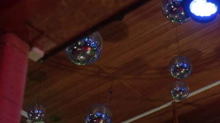 Mirror balls in a nightclub under the ceiling reflect light rays of different colors. Wideo