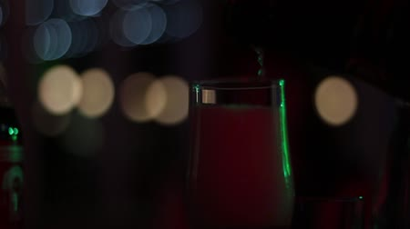 A mans hand pours a sparkling wine into a glass in the dark room of a nightclub. Wideo