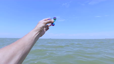 Metal hand spinner, or fidgeting spinner, rotating on guys hand against the background of the sea and ships on the horizon.