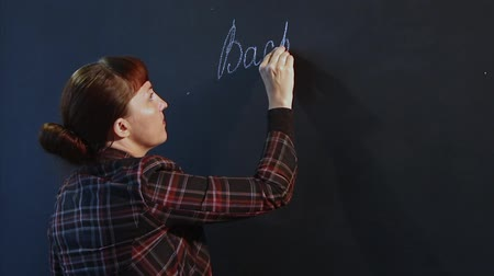 A pretty brown-haired teacher in a tartan jacket is writing with chalk on a blackboard.