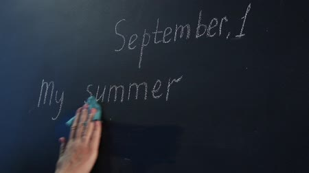The womans hand wipes the date and theme of the first lesson on the chalkboard. Close-up. Wideo