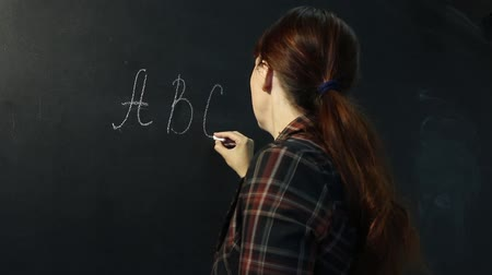 A beautiful young teacher of primary school writes ABC  on the blackboard and smiles cute. Wideo