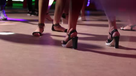 Girls are dancing in a nightclub. Beautiful legs on heels close-up.