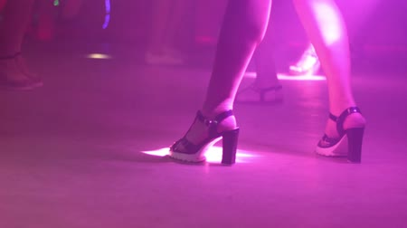 стриппер : Girl with beautiful legs on heels close-up dancing in a nightclub with bright light and smoke. Стоковые видеозаписи