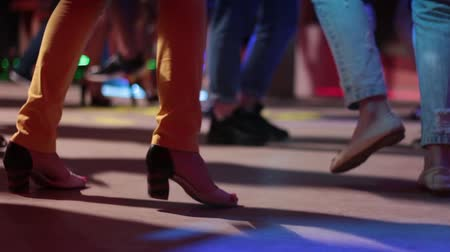 striptérka : A girl in light pants on heels and other people dancing in a nightclub with a bright light. Legs close-up.