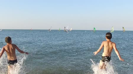 Slow motion. Two teenagers run into the water of the blue sea against the background of windsurfers on the horizon.