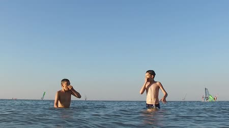Slow motion. Two teenagers are hiding in the water at sea.