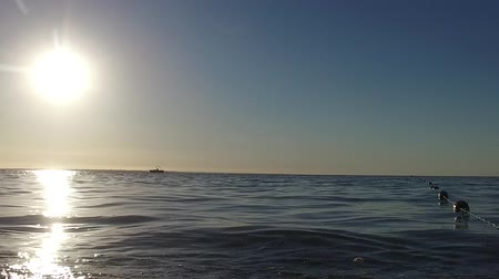 The camera turns from the sea dock to the buoys. The morning sun shines on the waves. Стоковые видеозаписи