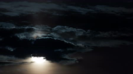 romsvetnik : Time-lapse. Full moon close-up rises through the clouds in the dark.