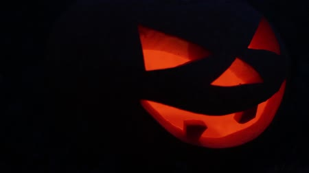 Jack-o-lantern from a pumpkin for Halloween close up glows and gradually becomes blurry.