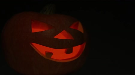 Pumpkin for Halloween with a candle inside blinks and gradually becomes blurry.