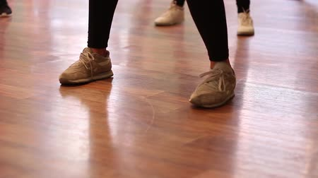 Training dance in the style of hip-hop. A view of the legs in the sneakers in the hall.