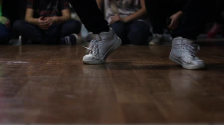 A girl in white sneakers dances on a battles in the style of a hiphop.