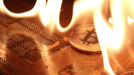 romsvetnik : The burning fire on the gold bitcoin on the motherboard.