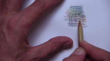 romsvetnik : A man draws a bitcoin coin with a multicolored pencil. Stock Footage