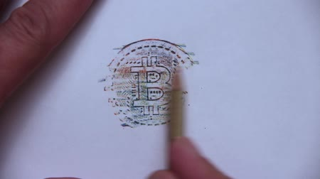 romsvetnik : A mans hand uses a full-color pencil to shade the bitcoin on a white sheet of paper. Stock Footage