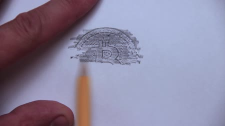 mevcut : The mans hand draws bitcoins on a white sheet of paper with simple strokes using a simple pencil.