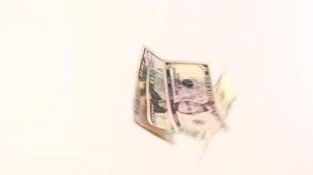 romsvetnik : Slow mo. Dollar bills of different denominations fall on a white background and fly apart in different directions. View from above. Stock Footage