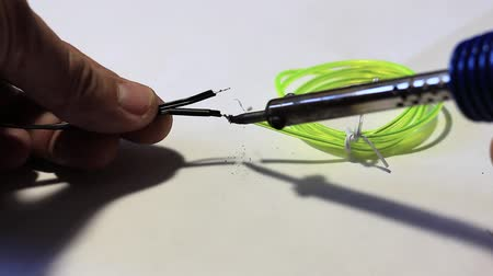вести : Close-up. The mans hands solder the black wire to the green one. Стоковые видеозаписи