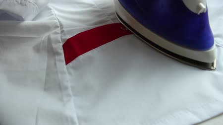 Close-up of ironing an electric iron of a white blouse with a red stripe. Стоковые видеозаписи