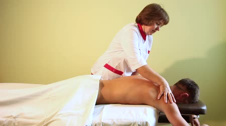 A nice woman massage therapist rubs the guys back before a therapeutic massage in the room with walls of light green color.