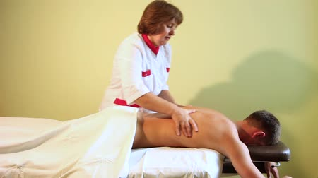 tényező : The guy receives massage from the woman-masseur in the room with the walls of light green color. Stock mozgókép