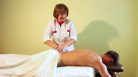 A female masseur in a medical dressing gown smiles sweetly when she is doing a massage to a sports guy. Стоковые видеозаписи