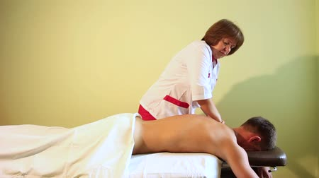 An element of relaxing back massage with female hands for a young man.