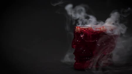 бурбон : A thick white smoke rises from a glass-skull with a red liquid. Mystical story for Halloween.