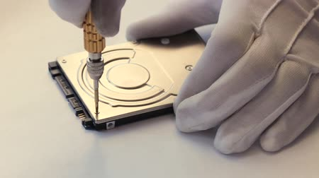 ações : A man in white gloves twists the screw on a computer hard drive with a screwdriver. Stock Footage