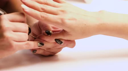 küfelik : The manicurist adjusts the shape of the nail of the thumb using an electric nail polishing tool in the manicure salon.