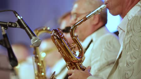 театральный : Close-up. A man in the foreground starts playing the saxophone with the other members of the brass band.