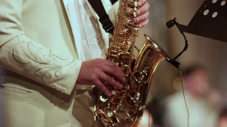 szakszofon : A musician in a white suit playing solo on a saxophone. Video from first sharpness to blurred at the end.