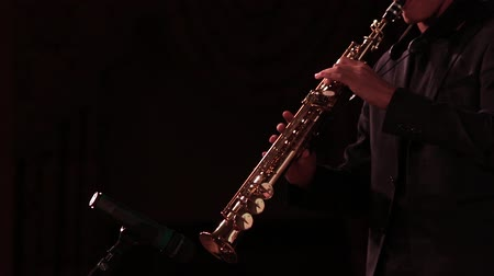 jazz festival : A man in a black suit plays music on a soprano saxophone on a dark background of the stage.