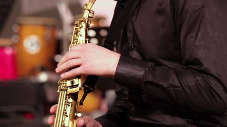danse jazz : A man with a beard in a black shirt. Emotionally plays the soprano saxophone. Close-up.
