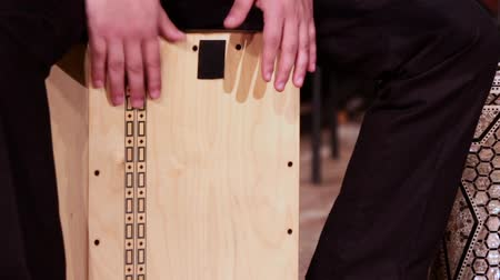 legs only : A drummer musician plays a percussion instrument Cajon. Footage on a musical theme.