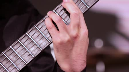 pankáč : A man is playing the guitar. Footage on a musical theme. A close-up of the left hand that puts the chords on the fretboard.