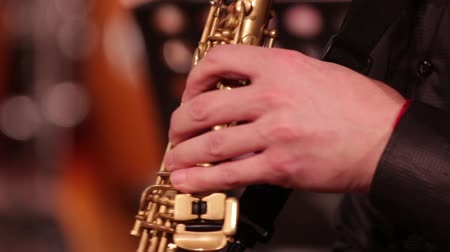 saxofon : Playing on a wooden instrument soprano saxophone. Close-up. The musician retrieves the sounds of music by clamping the keys and ends the game.