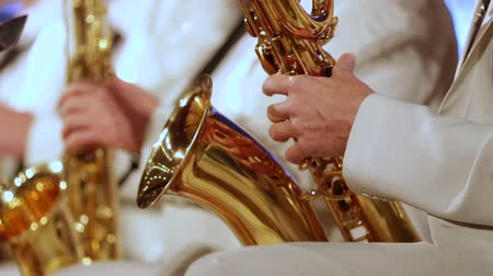 saxofon : A mans hand in a white suit on a gold saxophone in a jazz band. Close-up. Shallow depth of field.