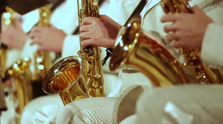 woodwind : A mans hands in a white suit on a gold saxophone in a jazz band. Close-up