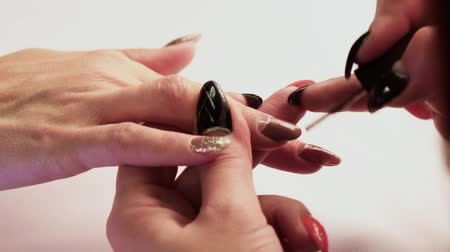 manikür : The manicurist makes the girls nails on her right hand with a brown lacquer. Close-up.
