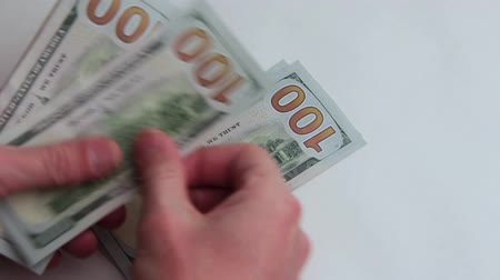баксов : Mens hands consider American hundred-dollar bills in the amount of one thousand dollars. Close-up. Concept. White background. Bribe or salary. Corruption or business.